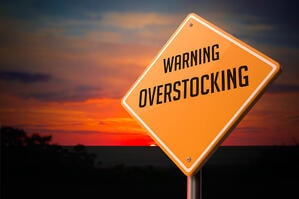 Overstocking on Warning Road Sign on Sunset Sky Background.